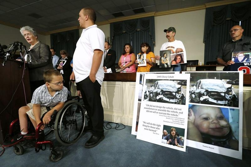 Trenton Buzard (2nd L) looks at a picture of himself as a toddler when he was paralyzed in a General Motors car crash, while at a news conference prior to testimony by GM CEO Mary Barra (not pictured) before a U.S. House Energy and Commerce Oversight and Investigations Subcommittee hearing on the GM ignition switch recall on Capitol Hill in Washington ,June 18, 2014. Buzard was injured in a crash in 2009 when his great-grandmother's car lost power and was struck head-on by another vehicle. Also pictured are former National Highway Traffic Safety Administration chief Joan Claybrook (L) and Trenton Buzard's father Robbie Buzard (3rd L) REUTERS/Jonathan Ernst (UNITED STATES - Tags: POLITICS TRANSPORT BUSINESS TPX IMAGES OF THE DAY) - RTR3UHHJ